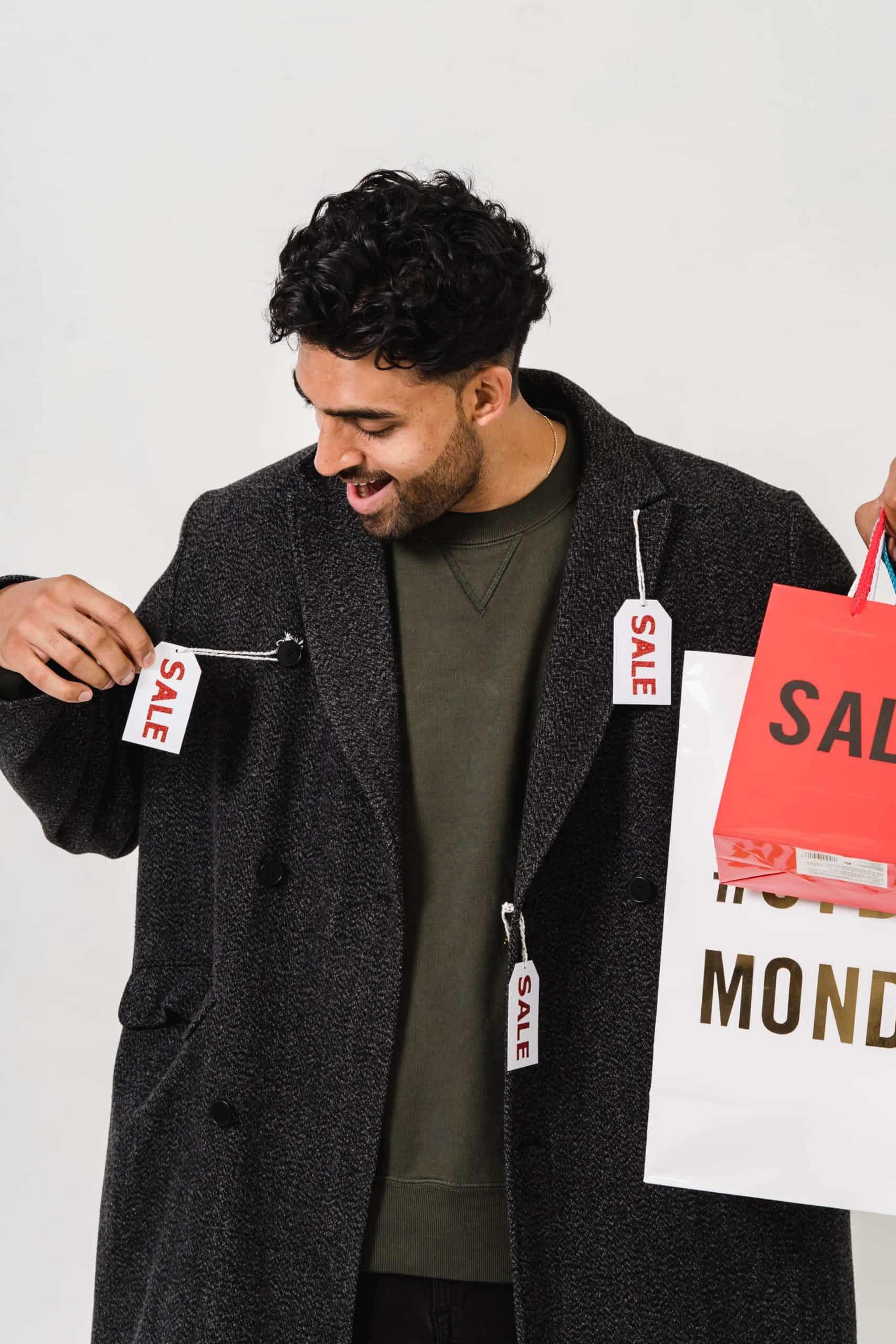 Mann in Mantel mit Preisschildern und Einkaufstaschen